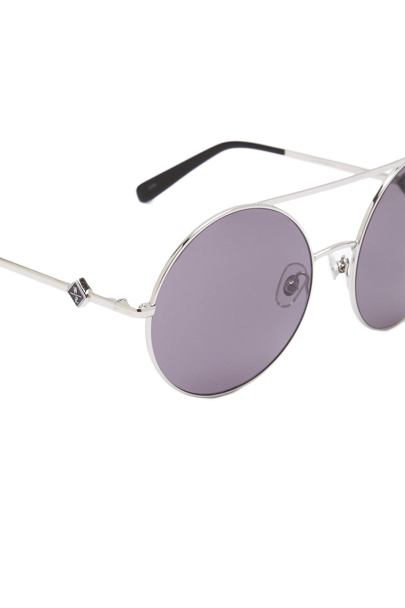 WONDERLAND SUNGLASSES Blythe Circular Tinted Sunglasses - Silver Sunglasses | Silver| Wonderland Sunglasses Blythe Circular Tinted Sunglasses - Silver Circular silver frame sunglasses with black tinted UV protective lenses. Double silver bar design adds a chic finish. Round frames are ideal to soften square face shapes. Frames are hand built using Italian Zyl acetate and French Cometec hinges. Carl Zeiss optics lenses provide 100% UV/UVB protection. Front View