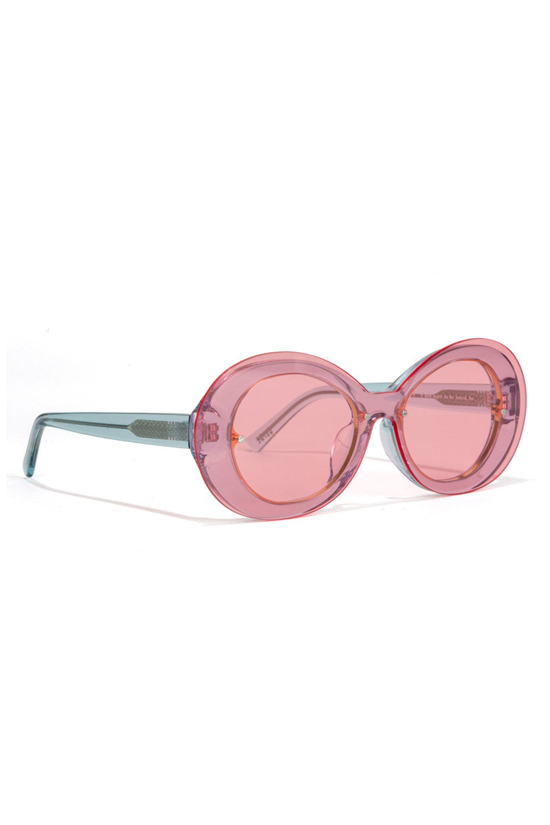 BONNIE CLYDE The Ai-Ren Sunglasses - Strawberry Bubblegum Sunglasses | Strawberry Bubblegum Pink| Angled View of Bonnie Clyde Ai-Ren Sunglasses in Strawberry Pink. This style goes particularly well with Heart, Square, Oval, & Oblong faces. Features: Oversize Lens  Lens Type: Grade A Nylon Fit Size: Small-Medium  Frame Color: Clear Blue Lens Color: Pink Tint Unisexual   100% UV Protection   Glare reduction   Scratch-resistant coating Made from Stainless Steel & Acetate