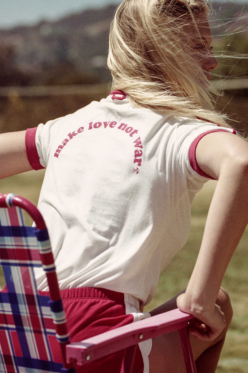 "CAMP COLLECTION Make Love Not War Tee - Vintage White W/ Red Trim Top | Vintage White W/ Red Trim| Camp Collection Make Love Not War Tee - Vintage White W/ Red Trim Back View V neck tee Short sleeves Red trim on sleeve & neckline Double red stripes on the sleeves   Heart Peace Sign Detail ""make love not war"" saying on the back"