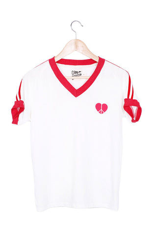 "CAMP COLLECTION Make Love Not War Tee - Vintage White W/ Red Trim Top | Vintage White W/ Red Trim| Camp Collection Make Love Not War Tee - Vintage White W/ Red Trim Front View V neck tee Short sleeves Red trim on sleeve & neckline Double red stripes on the sleeves   Heart Peace Sign Detail ""make love not war"" saying on the back"