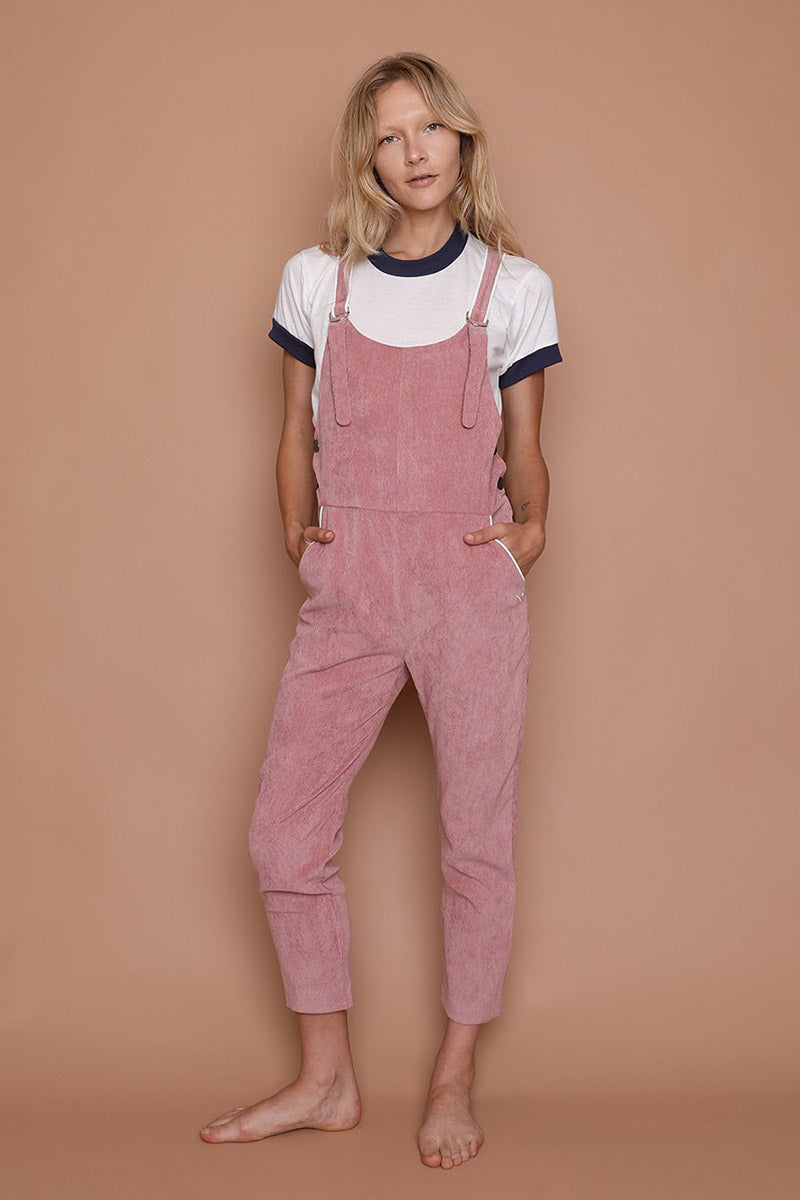 CAMP COLLECTION Picture Day Overalls - Dusty Pink Jumpsuit | Dusty Pink| Camp Collection Picture Day Overalls - Dusty Pink Front View Soft stretch corduroy overalls Cream piping details throughout Straight slim fit through the legs Cropped just above the ankle. Straps have D-rings for complete adjustability  Front and back pockets CAMP Double Flag embroidery on front left pocket   Functional buttons at hips Machine wash cold, lay flat or hang to dry 90% polyester / 8% nylon / 2% elastane