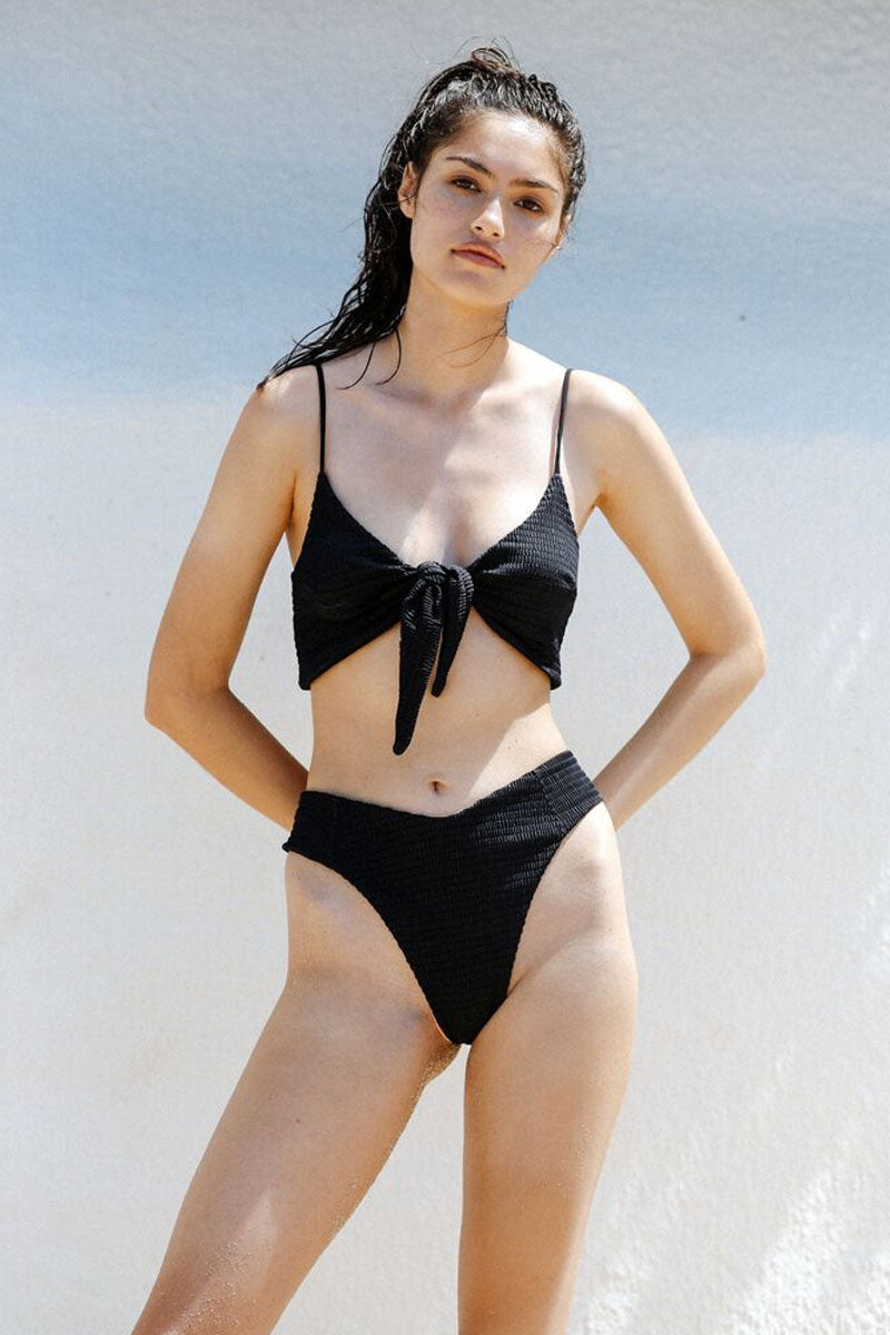 SIE SWIM Meghan Smocked Convertible Bikini Top - Black Bikini Top | Black| Sie Swim Meghan Convertible Bikini Top - Black. Features:   Can be worn front or back  Thin shoulder straps Front or back tie detail  Cinched detail  Made with love in the US Spandex/Nylon
