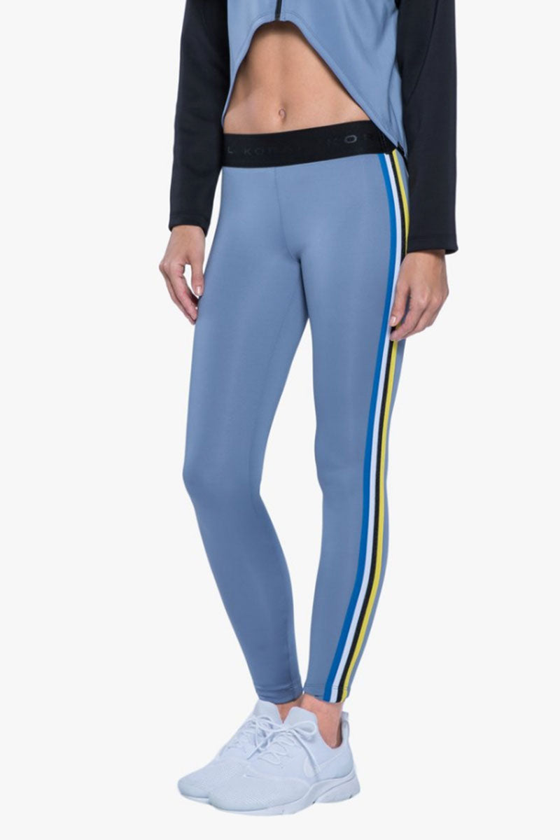 KORAL Rhys Leggings - Nova Blue Leggings |  Nova Blue| Koral Rhys Leggings - Nova Blue. Features:  Mid rise legging Side strap details Meant for athleisure Machine wash cold, inside out with like colors; No bleach; Tumble dry low MADE IN USA Side View