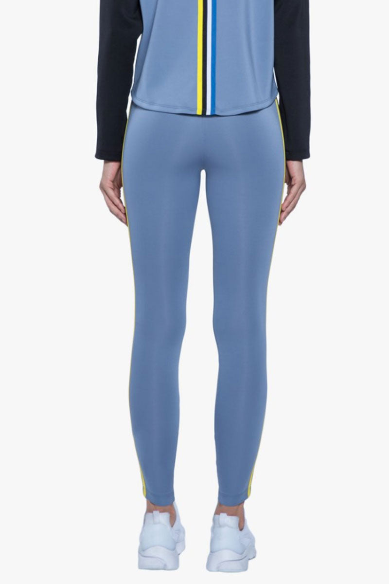 KORAL Rhys Leggings - Nova Blue Leggings | Nova Blue| Koral Rhys Leggings - Nova Blue. Features:  Mid rise legging Side strap details Meant for athleisure Machine wash cold, inside out with like colors; No bleach; Tumble dry low MADE IN USA Back View