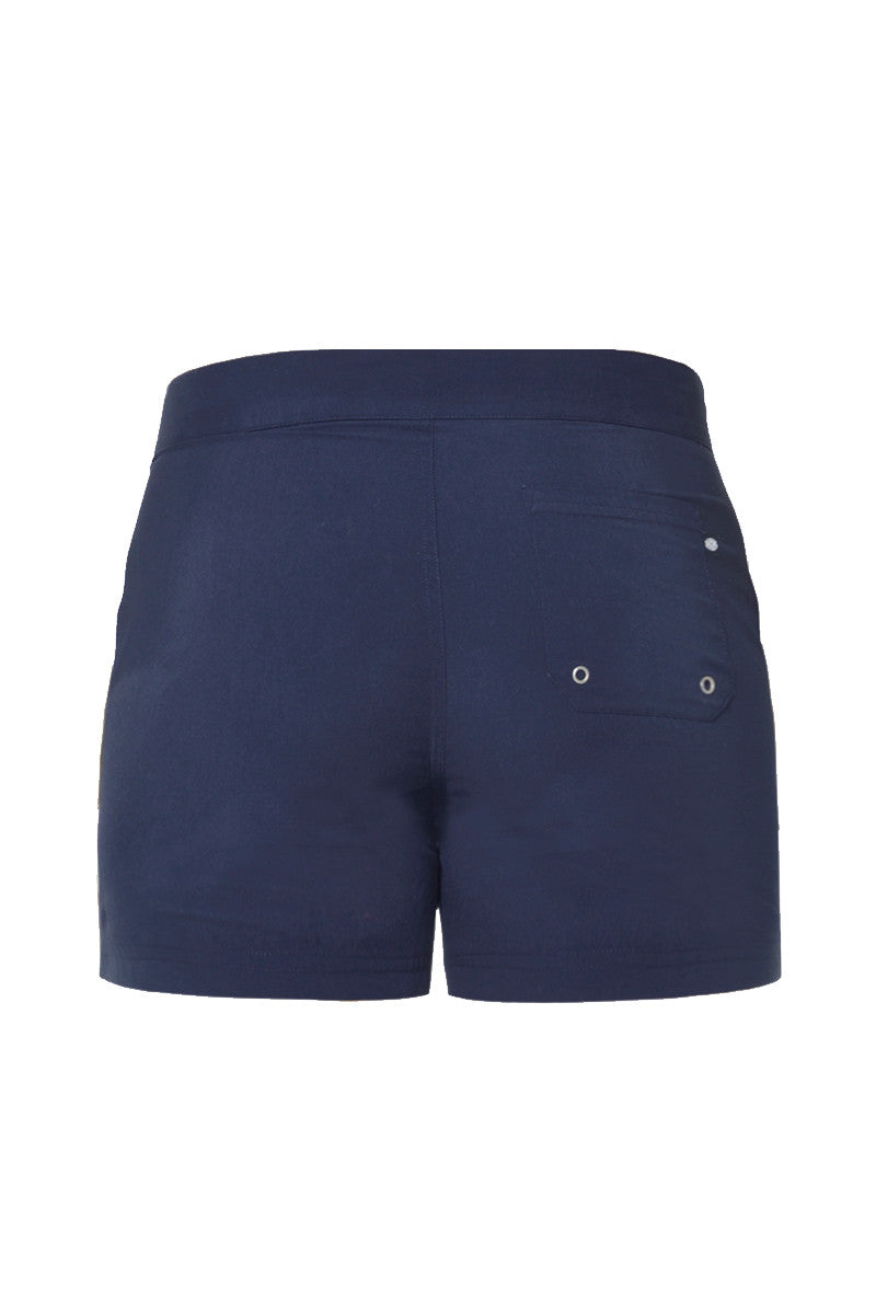 J.LIN Sailor Mid Length Swim Trunks - Classic Navy Mens Swim | Classic Navy| J. Lin Sailor Swim Sailor Mid Length Swim Trun0ks - Classic Navy. Flat Lay Back View. Mid-length  Buckle closure at center front  Forward seam with white pipping Snap front pocket, open back pocket White stretch lining   100% Polyester
