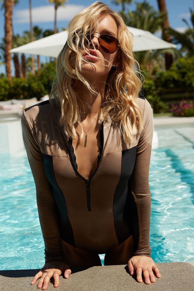 PILYQ Ace Zip Rashguard Bodysuit - Cadillac Nude/Black One Piece | Cadillac Nude/Black| Pilyq Ace Zip Rashguard Bodysuit - Cadillac Nude/Black Long Sleeve Rashguard Bodysuit  V Neckline  Zip Up Front Detail  High Cut Leg Full Coverage Colorblocking of Nude and Black Front View