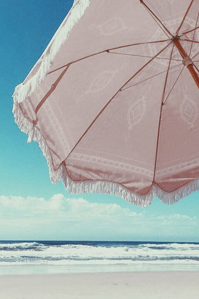 """BUSINESS AND PLEASURE CO Premium Beach Umbrella - Temple Pink Pool Accessories    Temple Pink  BUSINESS AND PLEASURE CO Premium Beach Umbrella - Temple Pink. Features:  Large 6"""" Span. Printed poly/cotton canvas with UV & Water Resistant treatment. World forestries certified, reclaimed timber wood Pole with Chestnut finish. Natural cotton Fringe & Internal trim. Canvas Carry Bag in same print design. Natural cardboard gift box. Front View"""