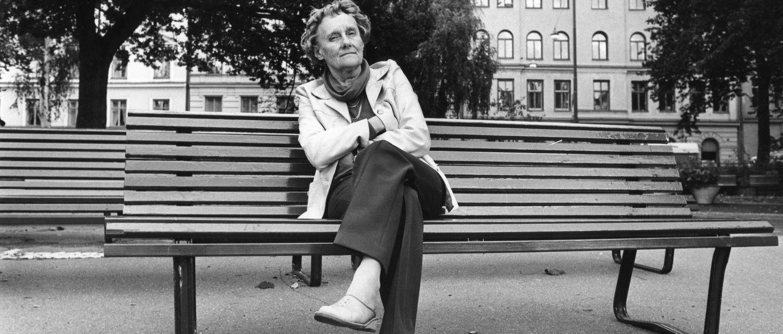 Astrid Lindgren sitter på bänk