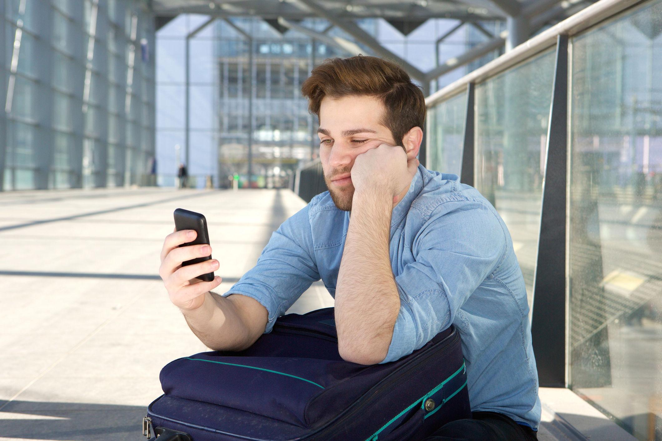 Mensch schaut gelangweilt auf sein Smartphone