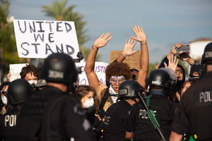 Protesters with hands up in front of police