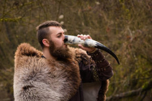 Nordic man drinks mead from horn