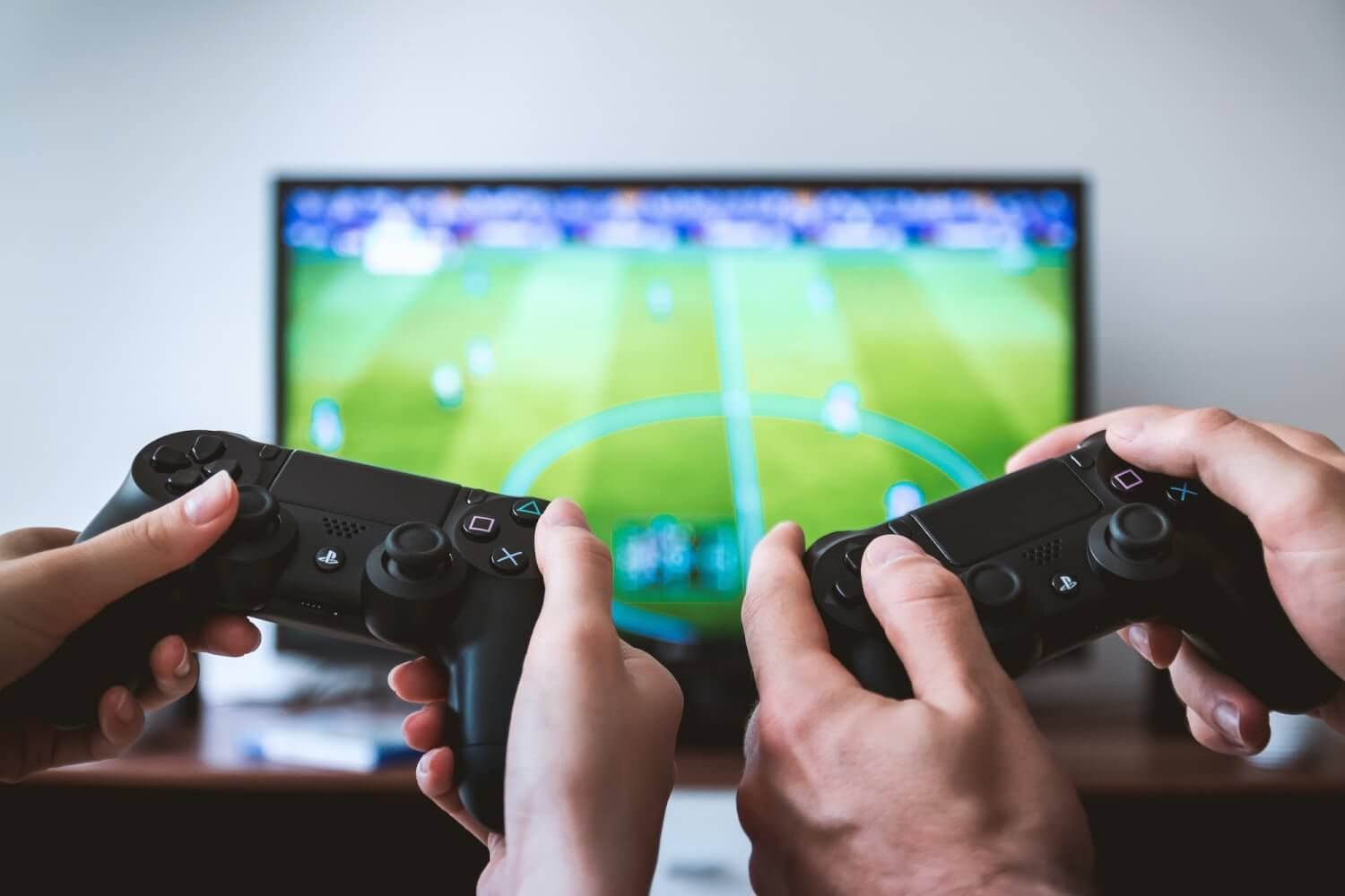 Two hands holding games console controllers in front of a TV screen