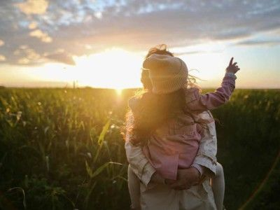 Woman holding child, walking through a field