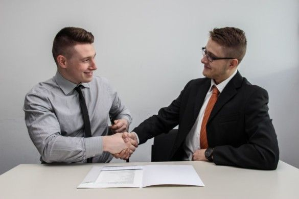 Two people sitting at desk shaking hands