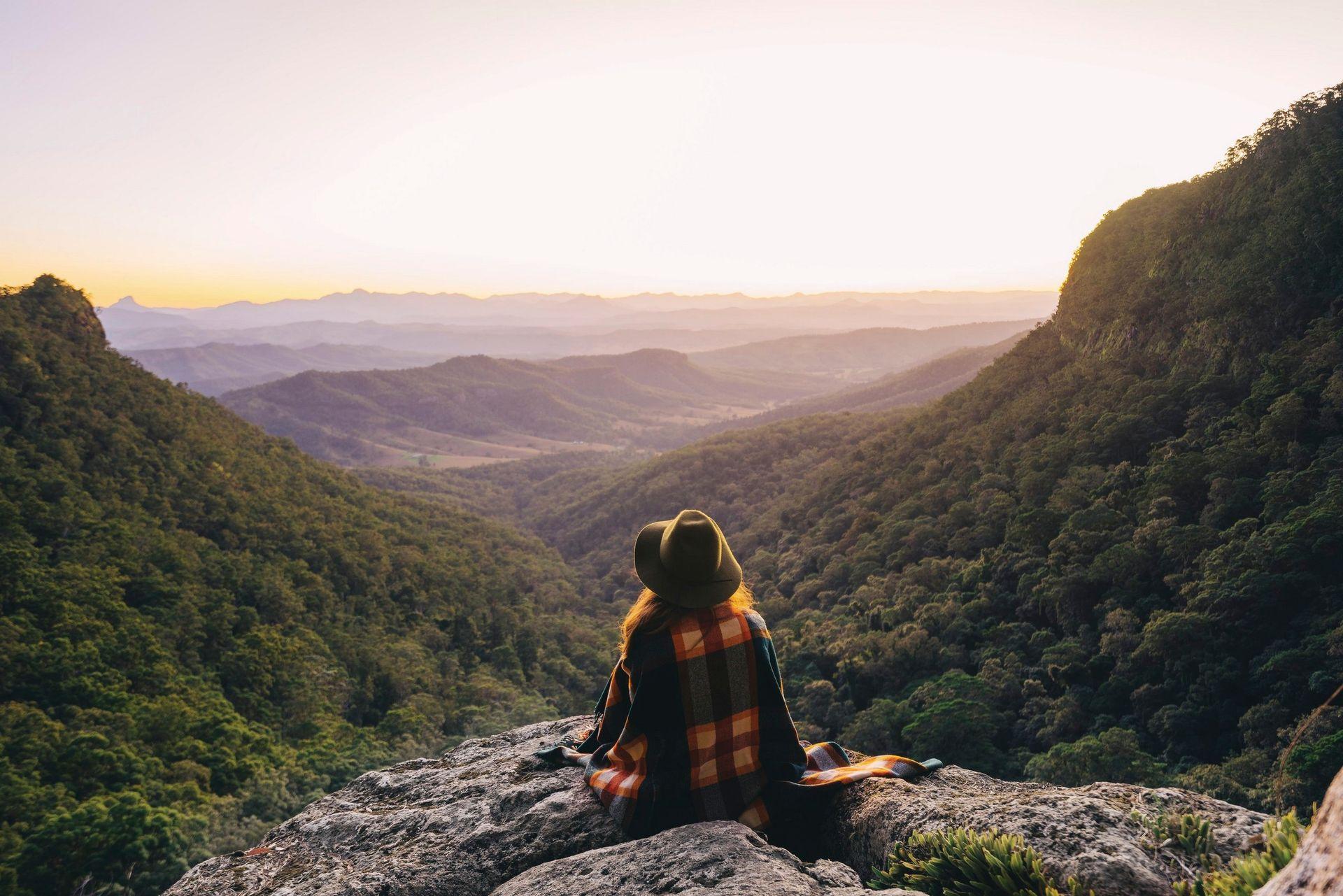 Meisje met een hoed zit te genieten van het uitzicht van de Tablelands.