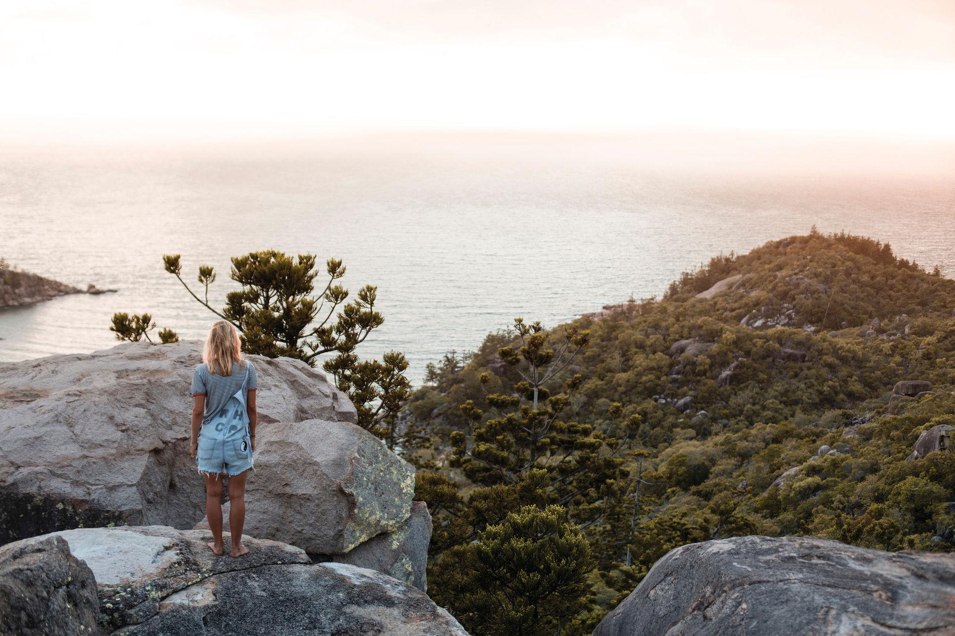 Meisje in een spijkerbroek kijkt naar de zonsondergang op de rotskust van Magnetic Island aan de Oostkust van Australië.