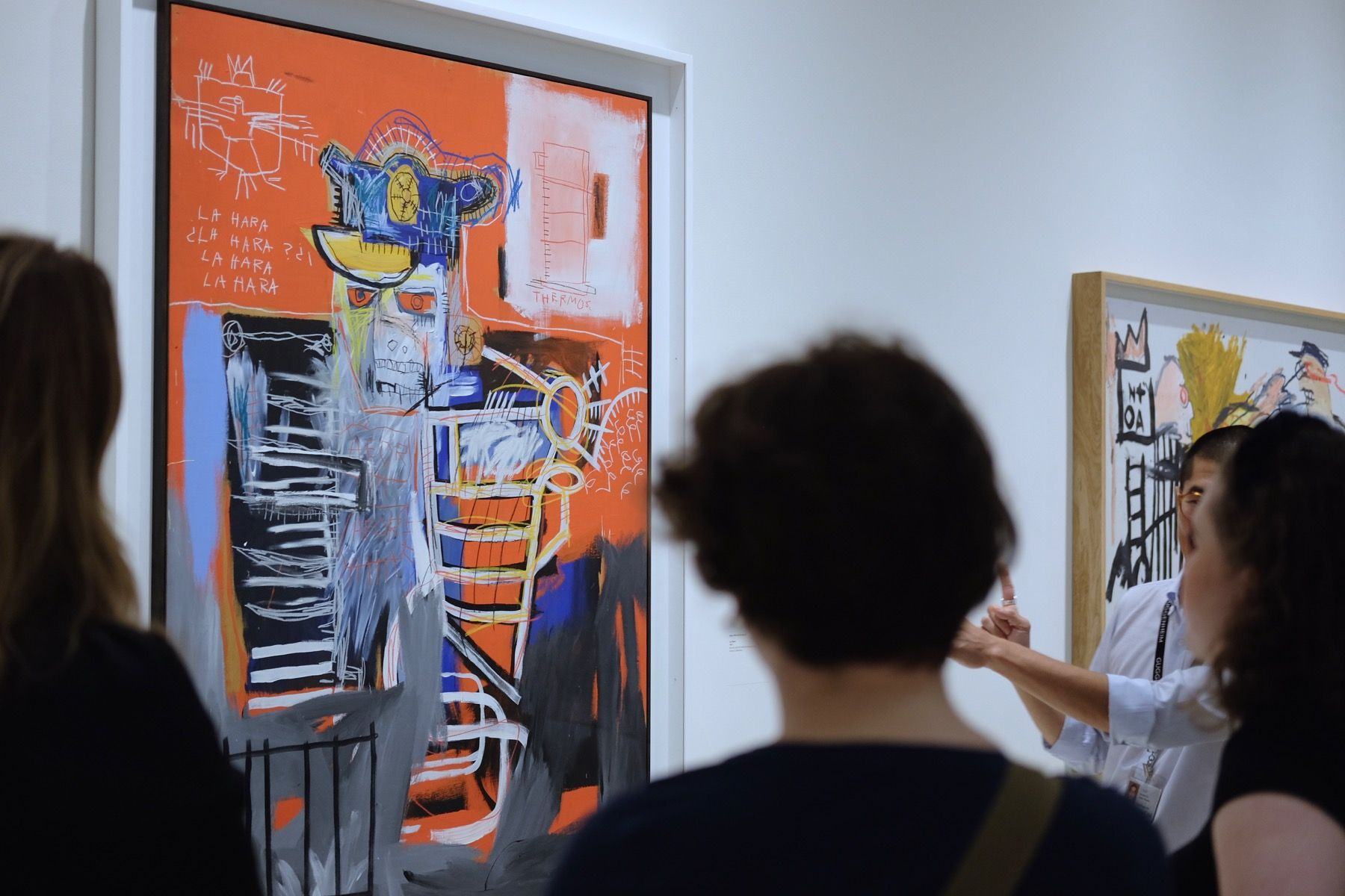 A museum guide explaining a Basquiat painting to people.