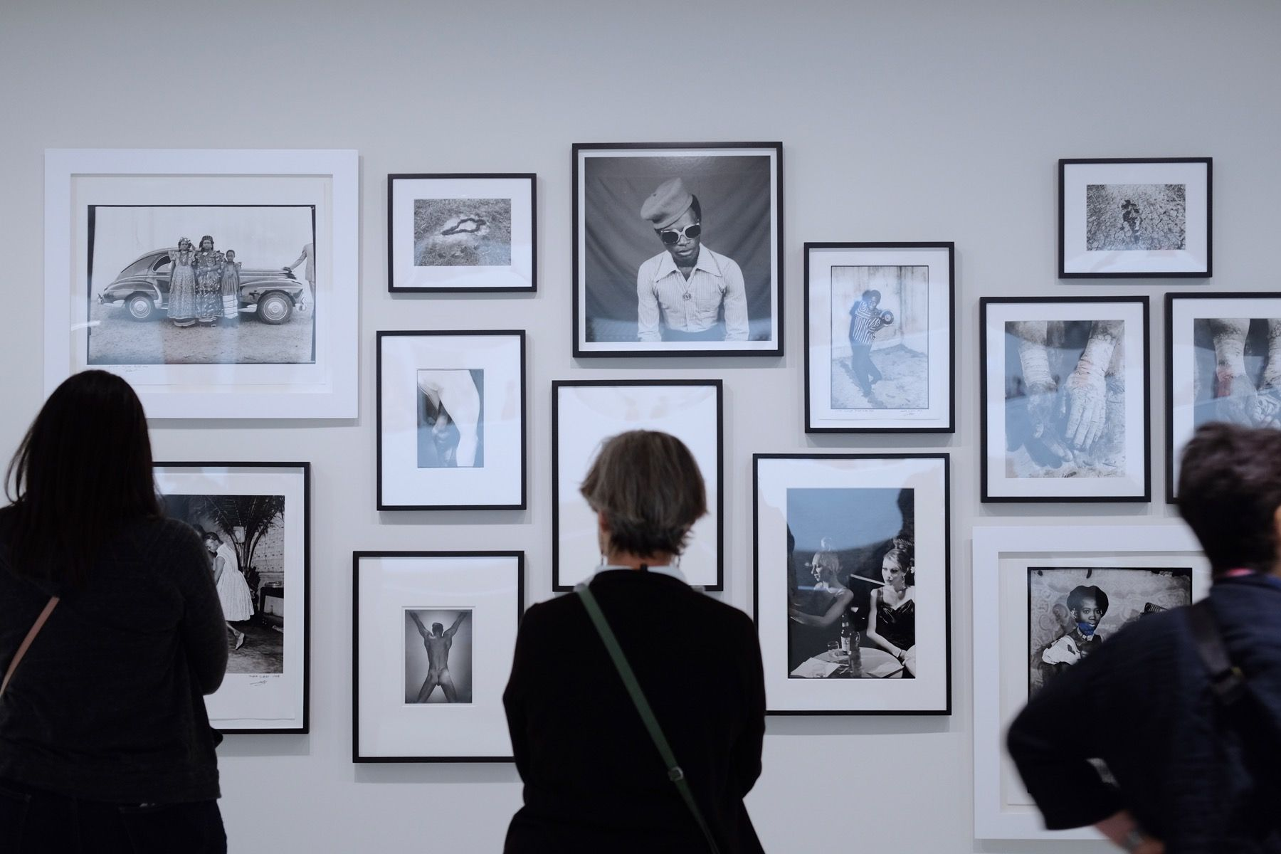 A lady looking at a series of portraits, with her back to the camera.