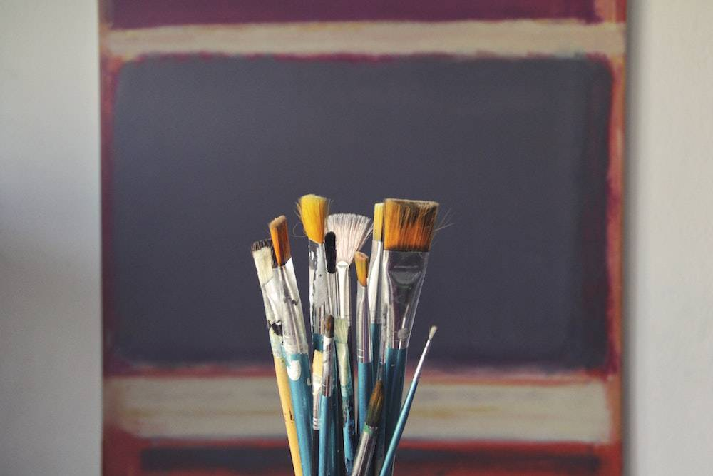 a bucket of paintbrushes