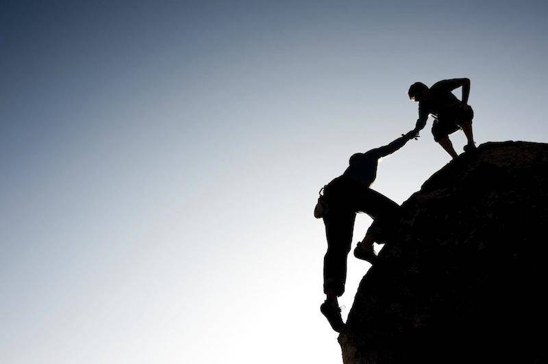 person helping another person up a mountain
