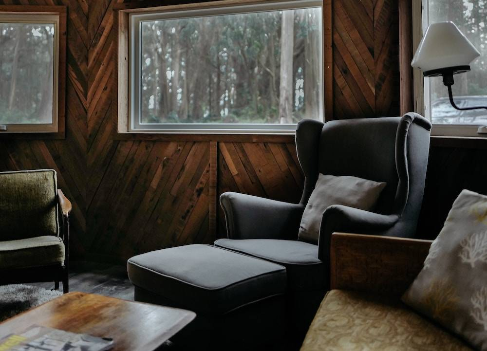 things to do on staycation - a cozy chair in a living room with wood panel walls