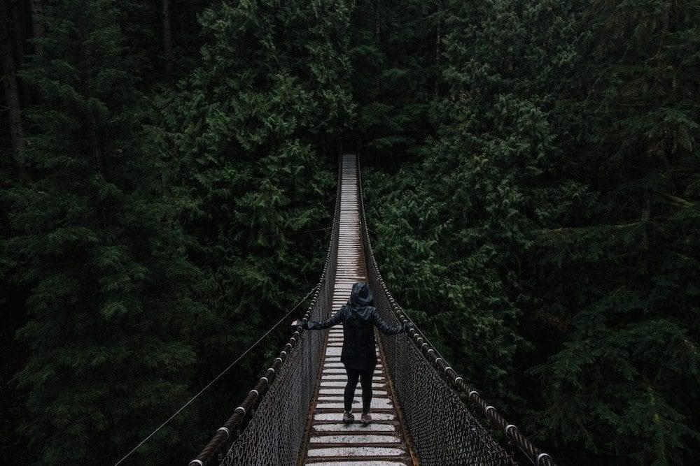 woman facing her fear crossing a bridge