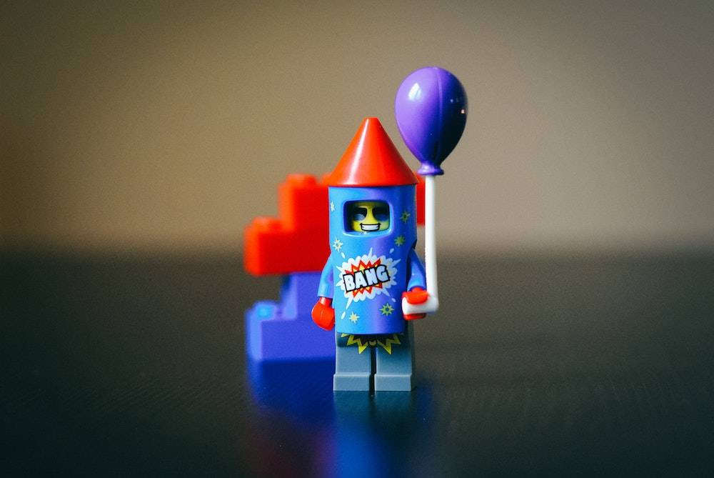 little lego person wearing a fire cracker outfit holding a balloon
