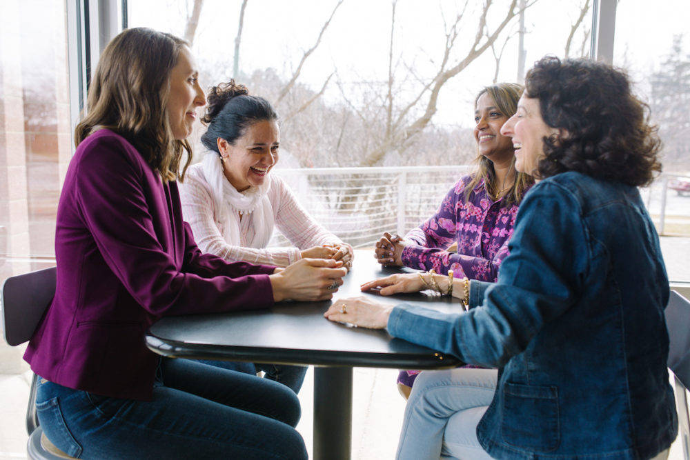 A group of women entrepreneurs sitting together at a coffee shop laughing