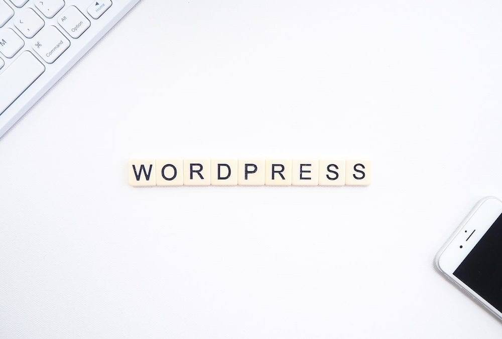 best plugins for wordpress - tiles on a desk spelling out wordpress with computer keyboard and phone nearby