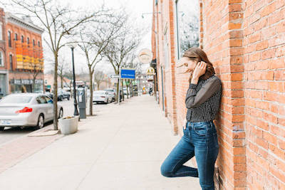 mindful self compassion: woman standing downtown against a brick wall looking downward