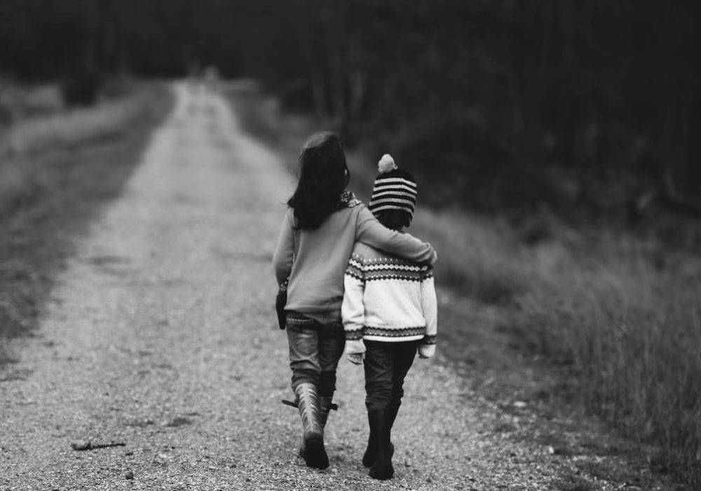 Self Care for Entrepreneurs: two young children walking down a dirt road arm in arm