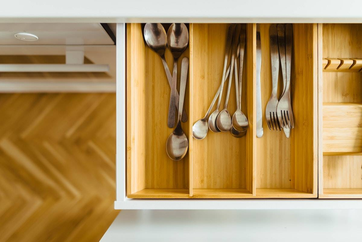 How to Feel Happy Again: silverware inside a wooden drawer in a white kitchen
