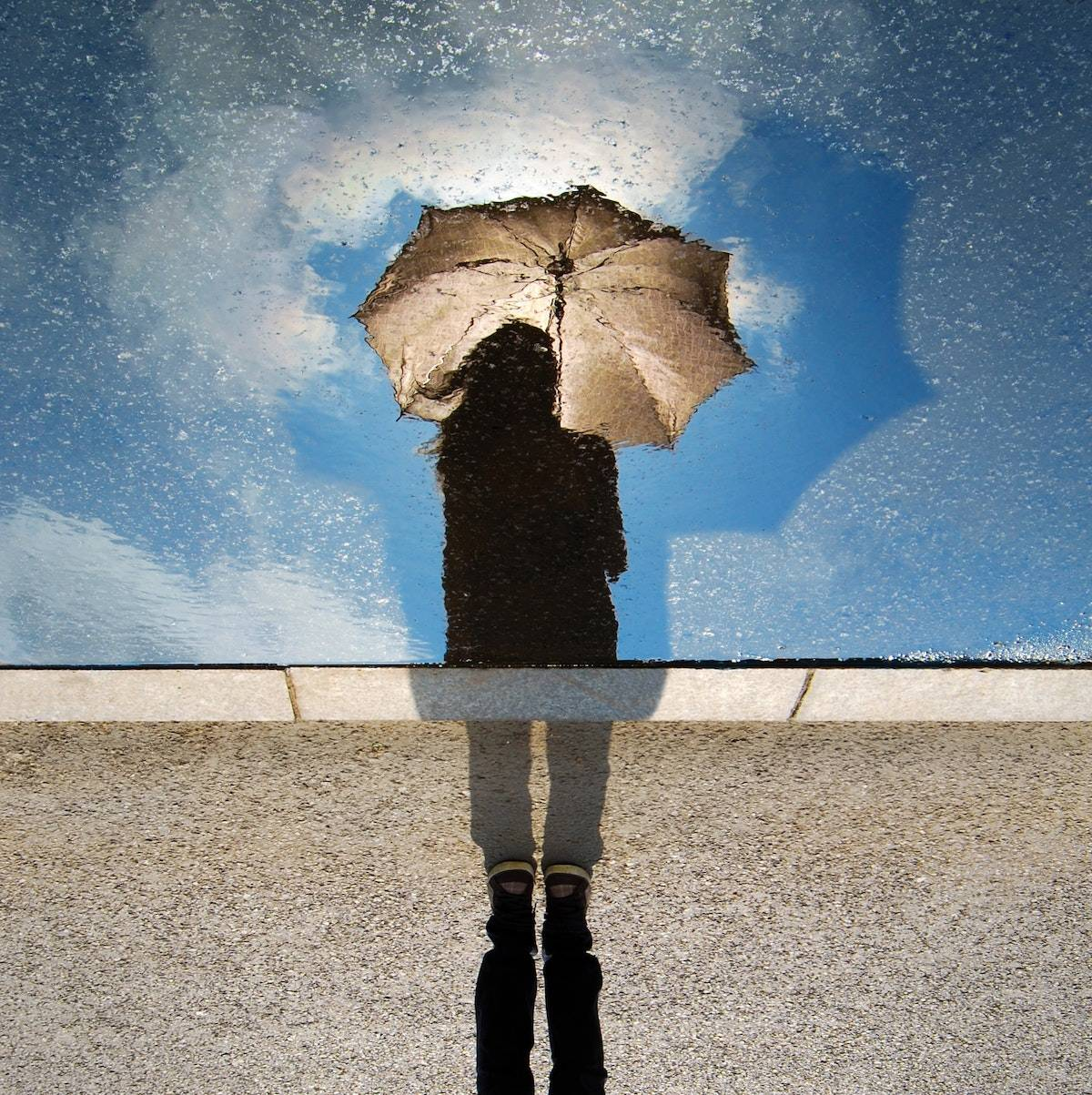 life before COVID: reflection in a puddle of a woman holing an umbrella, bright blue sky behind her