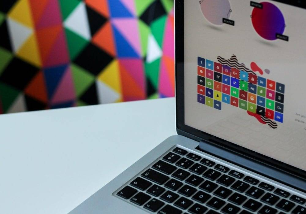 Cool WordPress Plugins: a laptop on top of a table with a very colorful wallpaper in the background