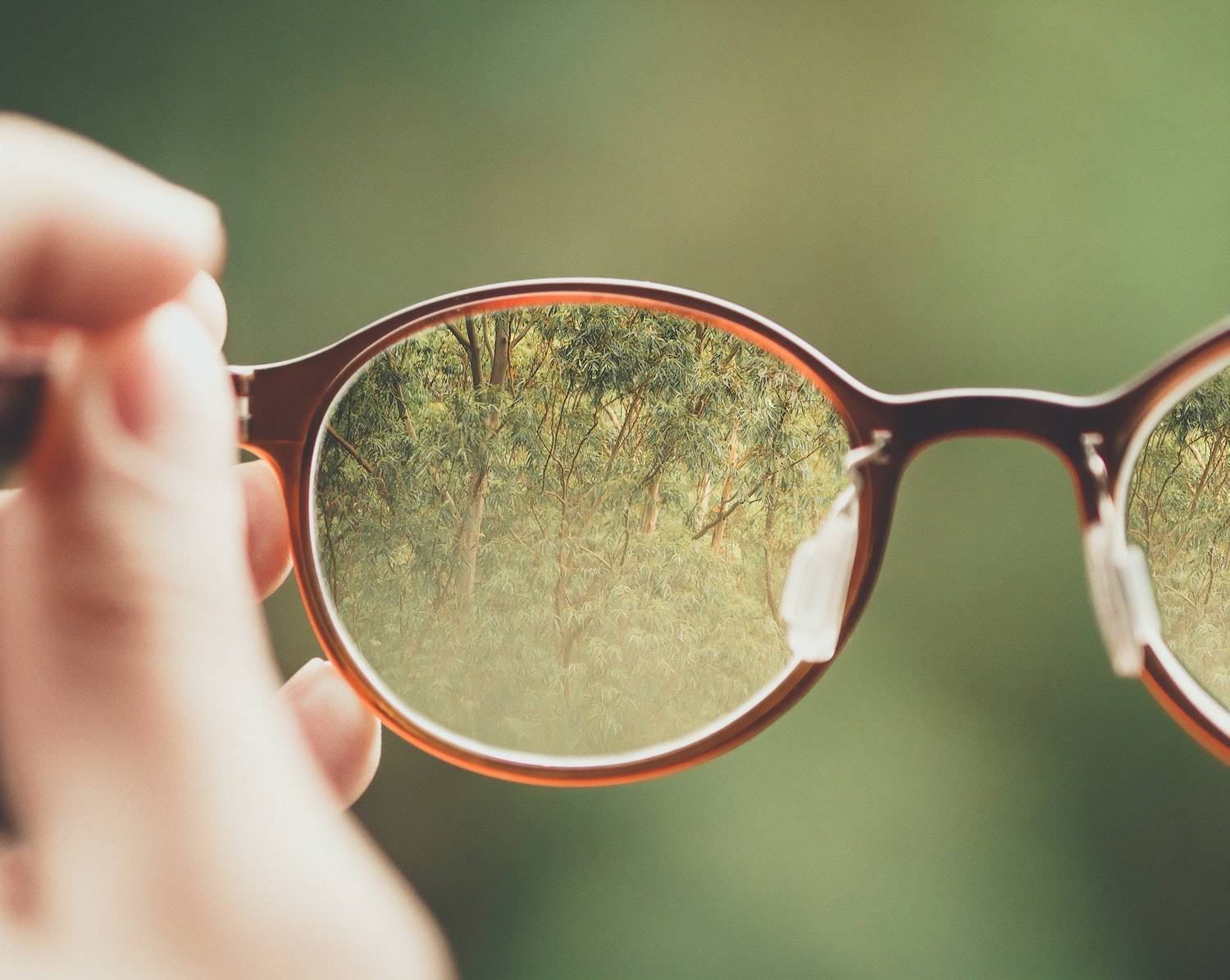 life lessons learned: someone looking through a pair of glasses that they're holding