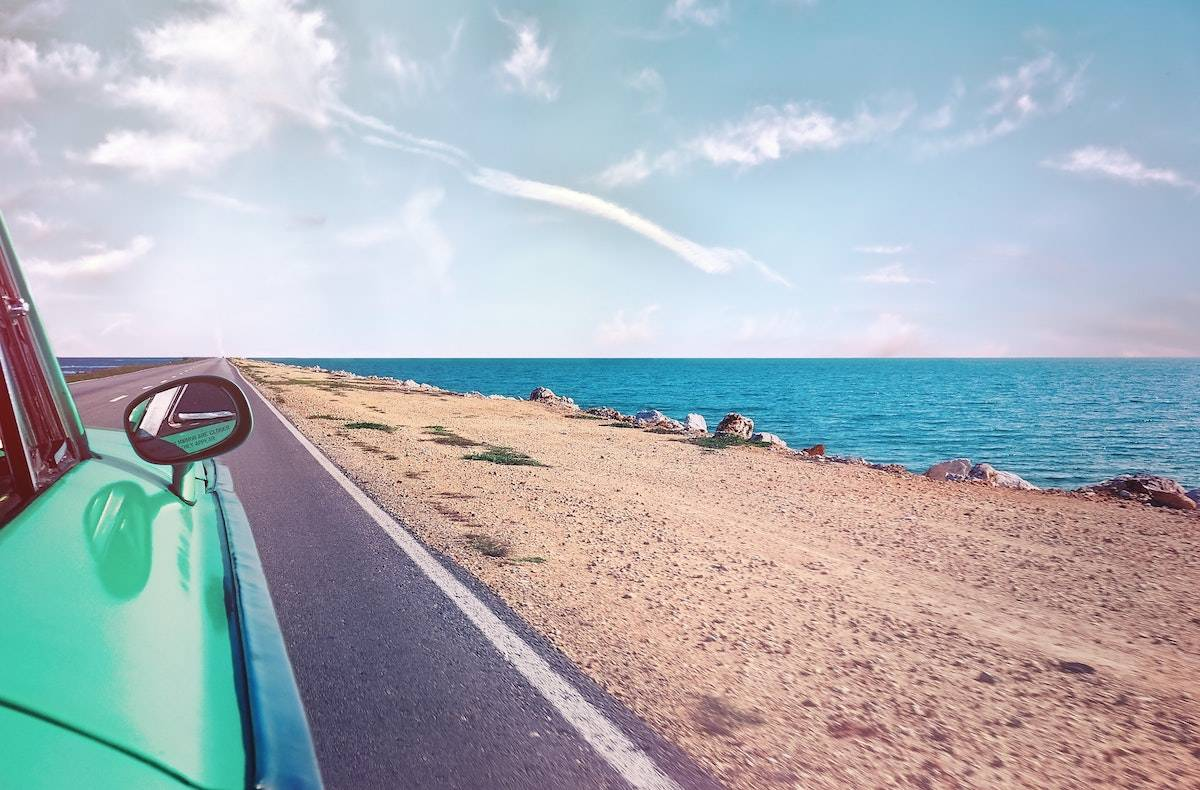 how to have the best vacation ever: teal car driving by the sand and the ocean