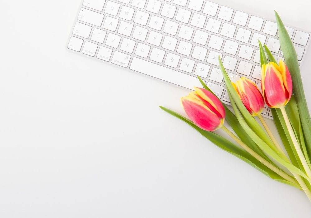 website content ideas: bouquet of tulips laying on top of a white computer keyboard