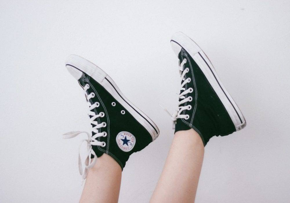 creative website ideas: two feet sticking up in the air, wearing black converse