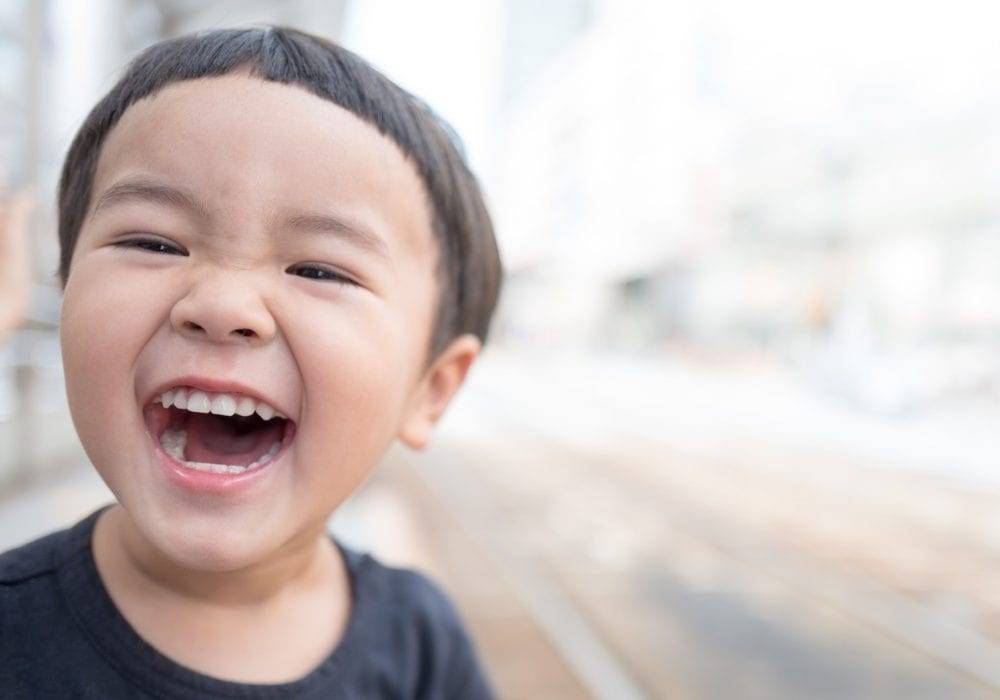 how to laugh more: a young Asian boy laughing and smiling