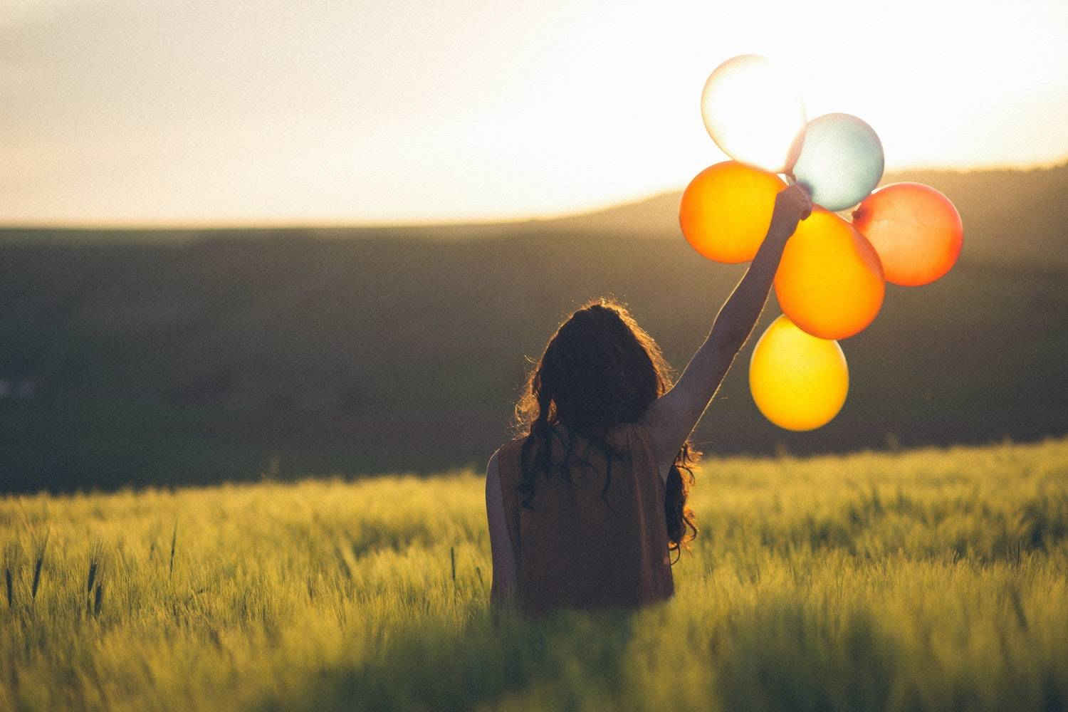 how to find happiness again: woman holding up a bouquet of baloons in a field at sunset