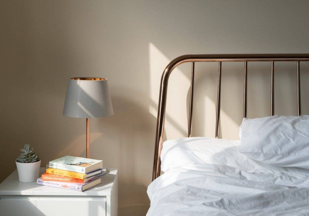 How to get the best sleep at night: a relaxing bed, nightstand and lamp with morning light pouring in