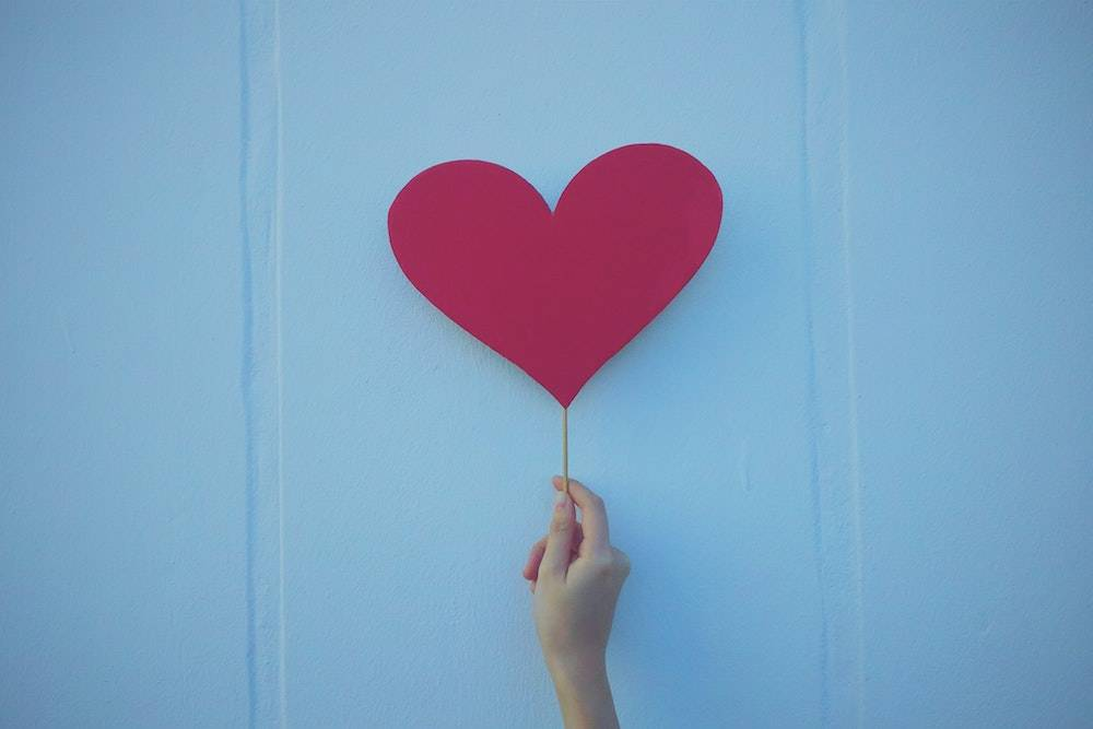 What pages should I have on my website? person holding up a red paper heart