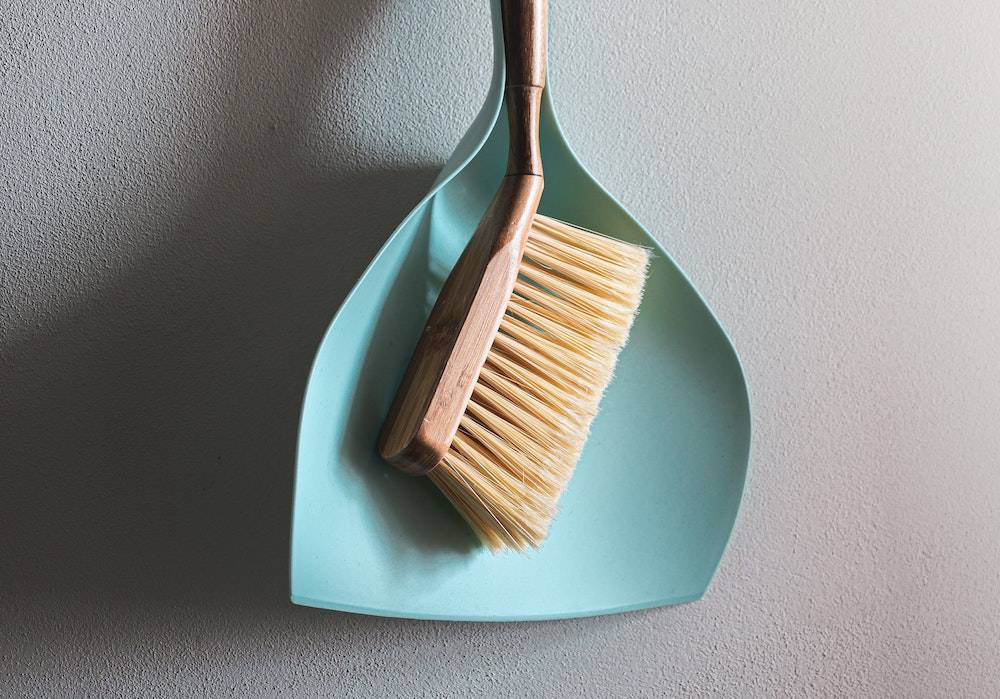 a dust pan and brush hanging from the wall