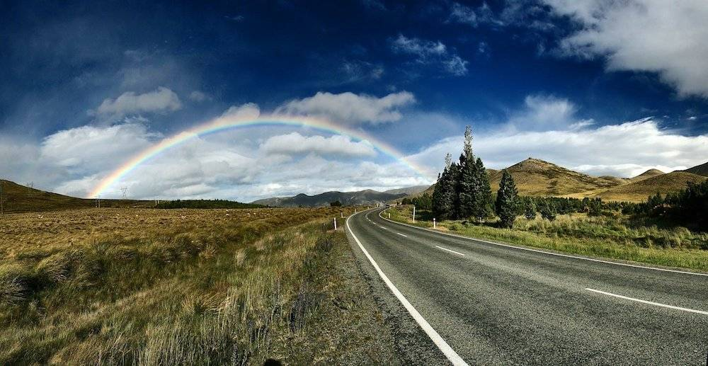 a beautiful country road with rainbow
