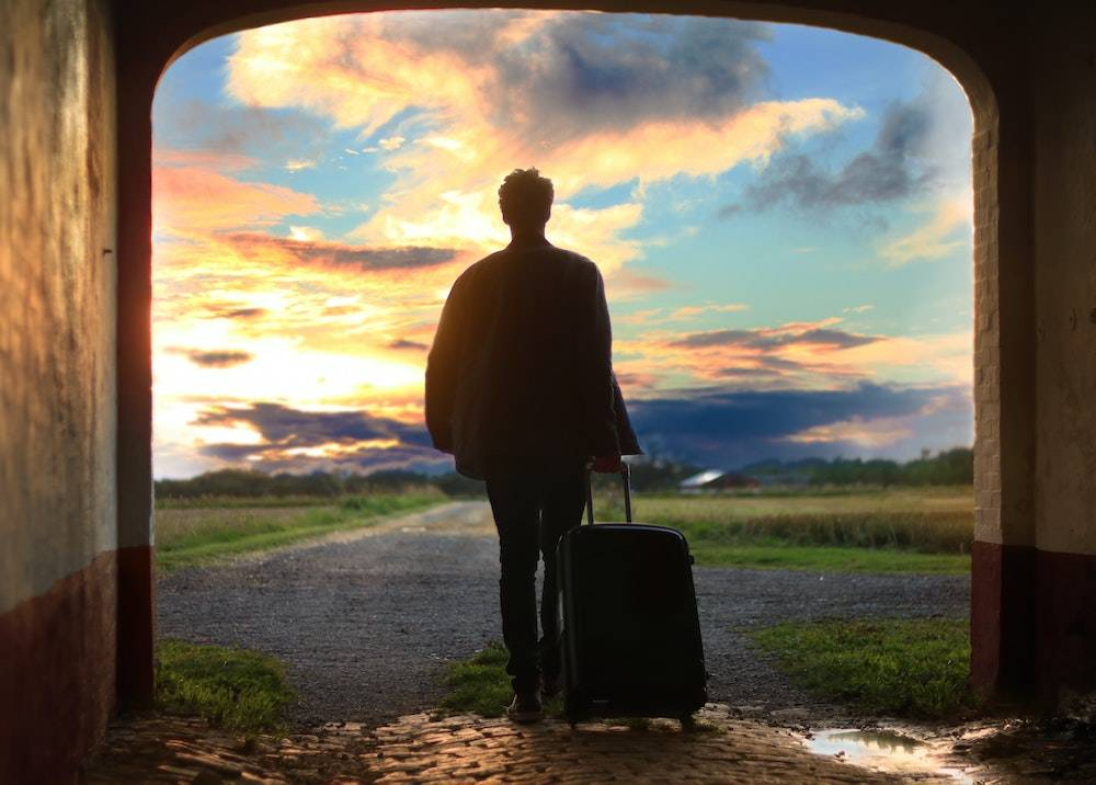 travel tips and tricks: woman heading into a sunset pulling a suitcase