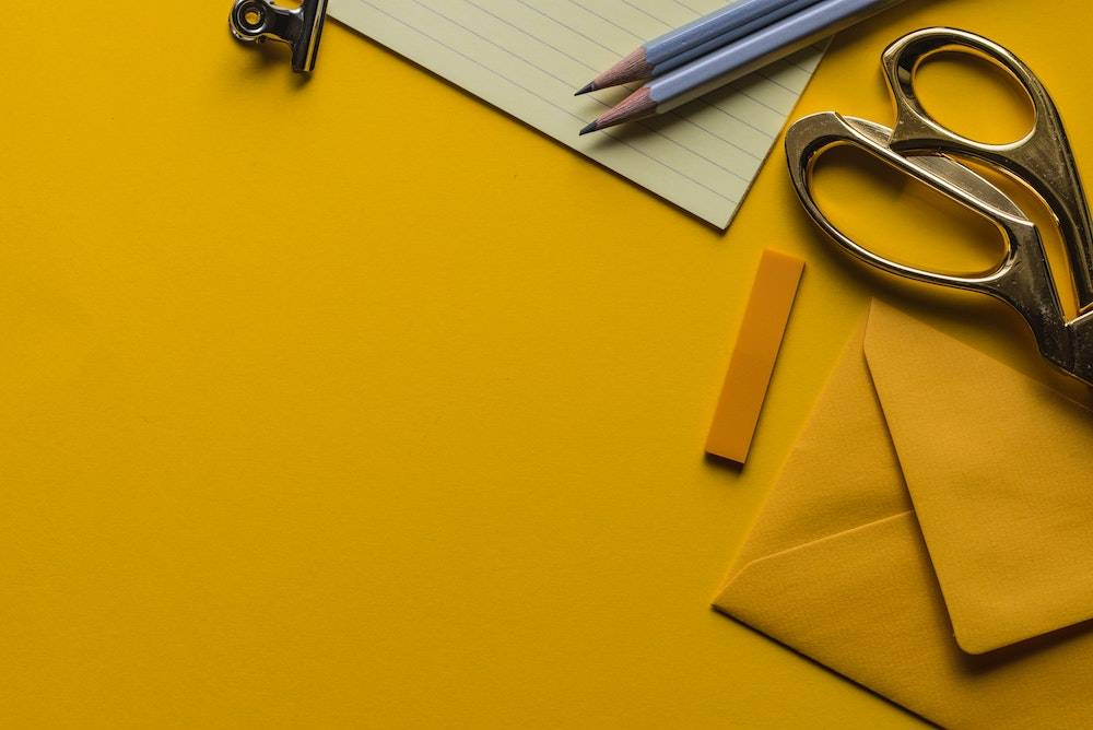 website color psychology - yellow table with yellow envelope, scissors, paper, and pencil