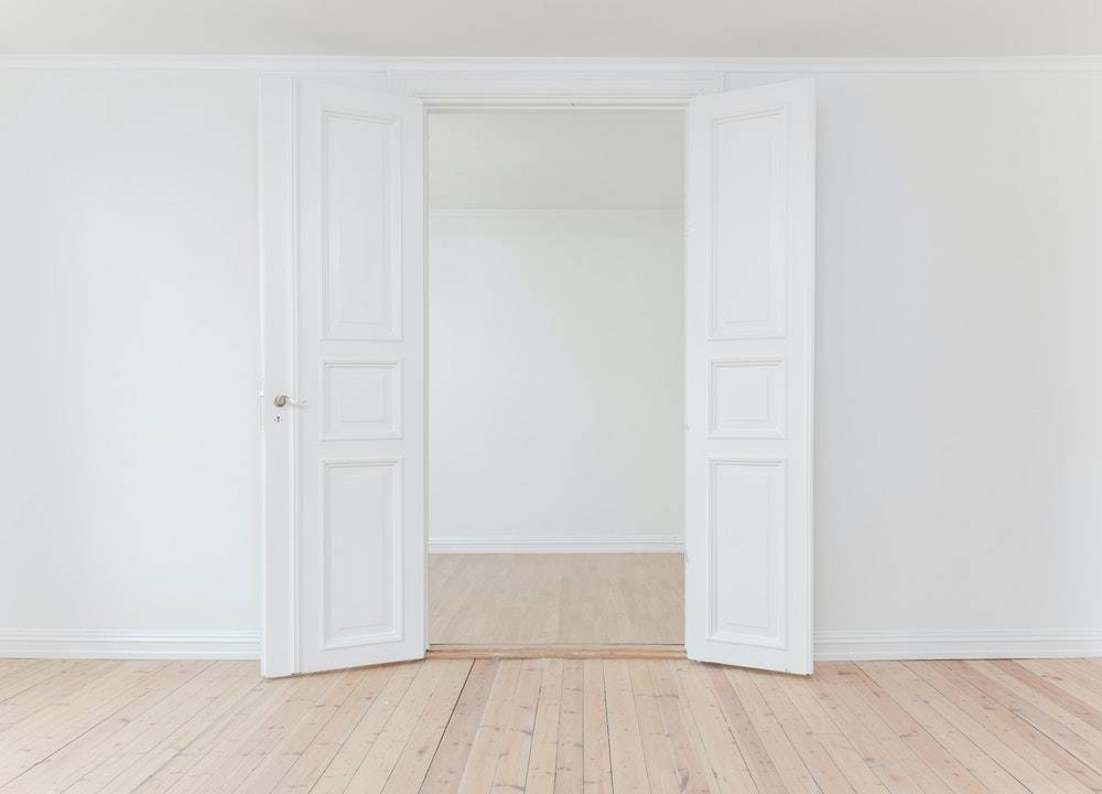 Begin living a minimalist lifestyle - two white doors opening up to an empty white room