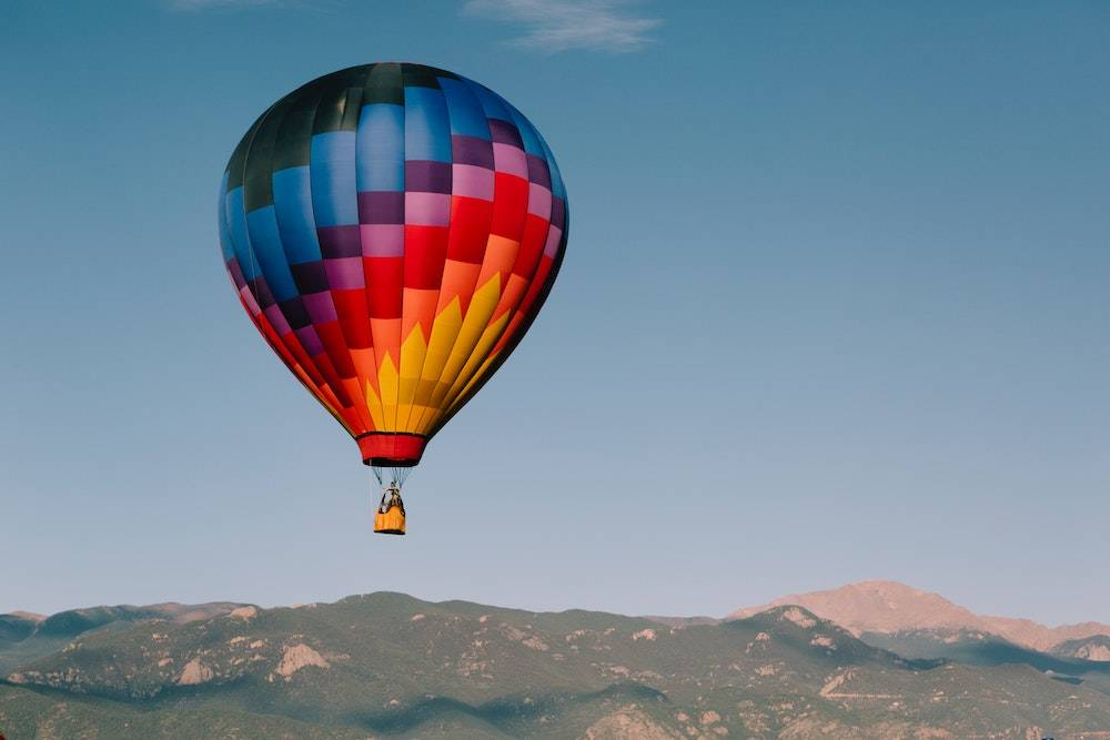 website color psychology - rainbow hot air balloon flying over the desert