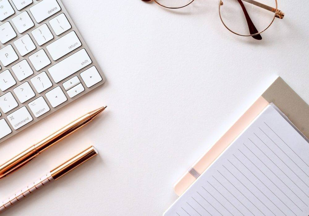 your personal brand - desk with keyboard, notepad, and pens