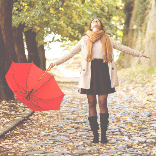 woman standing in the autumn in the park with a red umbrella holding her hands out and looking towards the sky happily